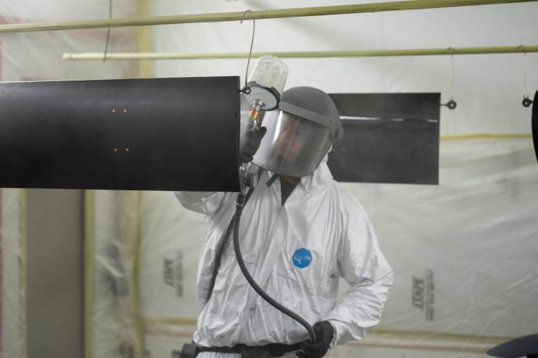 man spray coating carbon fibre part